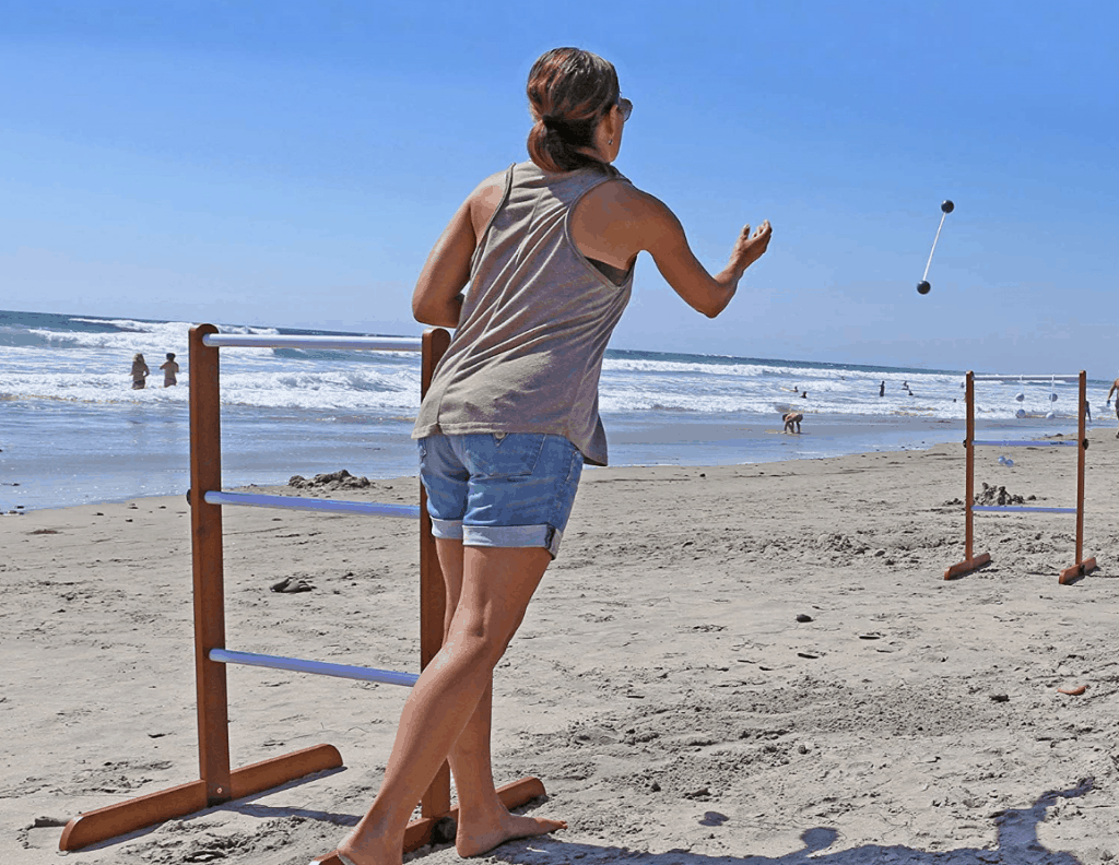 woman playing ladder golf at the beach