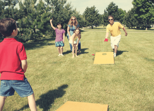 family playing corn hole backyard