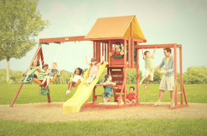 family playing outdoors in the cedarbrook wooden playset
