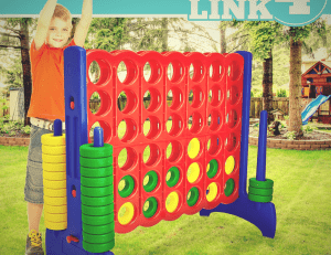 kid playing life size connect 4 in backyard