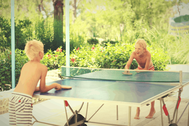 two kids playing ping pong outdoors